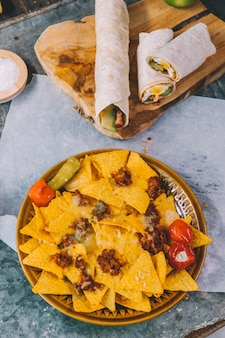 Top view of mexican nachos tortilla chips in plate with mexican tacos on cutting board
