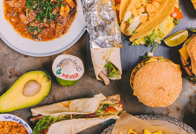 Top view of mexican tacos; beef dish; avocado and burger over old metal background