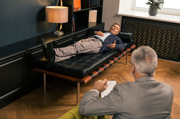 Top view of a middle-aged man lying on the couch talking to a male psychotherapist in his office