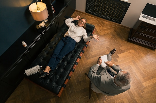 Top view of a middle-aged woman lying on the couch while talking to her psychotherapist in his office
