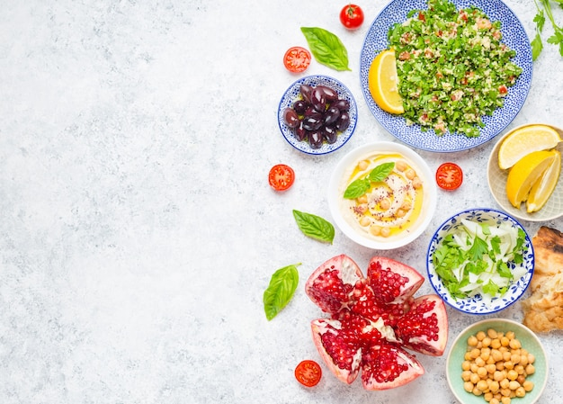 Top view of middle eastern or arab dishes and assorted meze and snacks on concrete white background