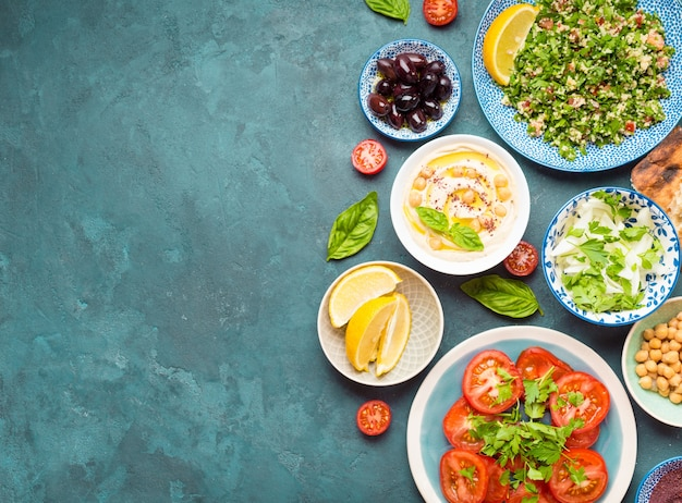 Top view of middle eastern or arab dishes and assorted snacks on concrete background with copy space