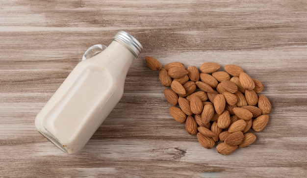 Top view of milk bottle and almonds