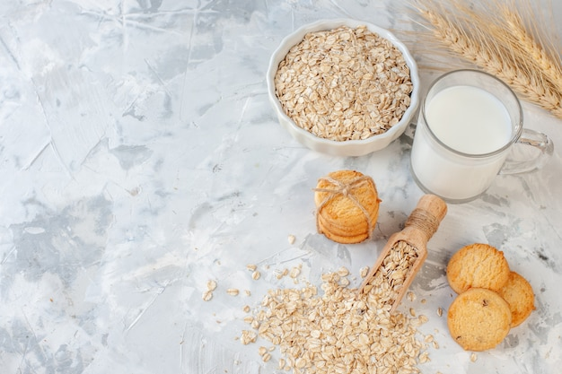 Top view milk bottle and milk glass cookies oats bowl wheat spikes on grey background copy place