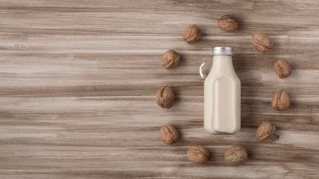 Top view of milk bottle with walnuts and copy space
