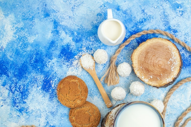Top view milk bowls wood boards coconut balls coconut powder in wooden spoons rope cookies on blue white background