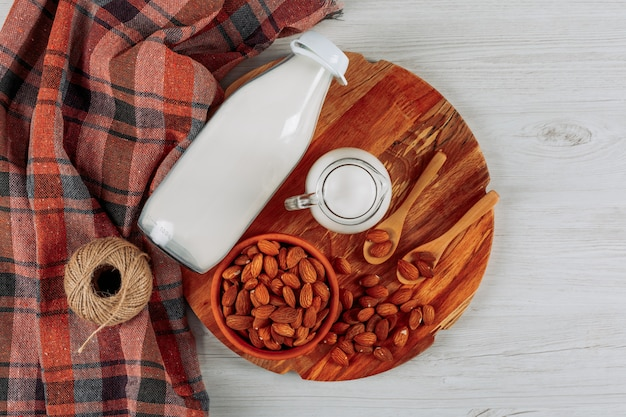 上面ビューミルクデカンタと白い木製の織り目加工の布の背景に木の板にアーモンドのボウルとボトル。横型