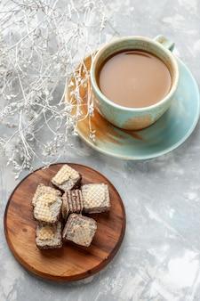 Вид сверху молочный кофе вкусный с шоколадными вафлями на светлом столе сладкое сахарное вафельное печенье