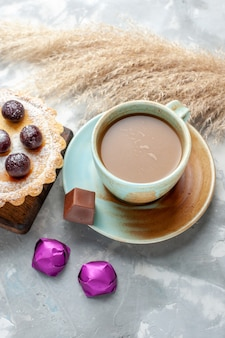Top view milk coffee with cherry cake and candies on the light table cake biscuit sweet sugar bake