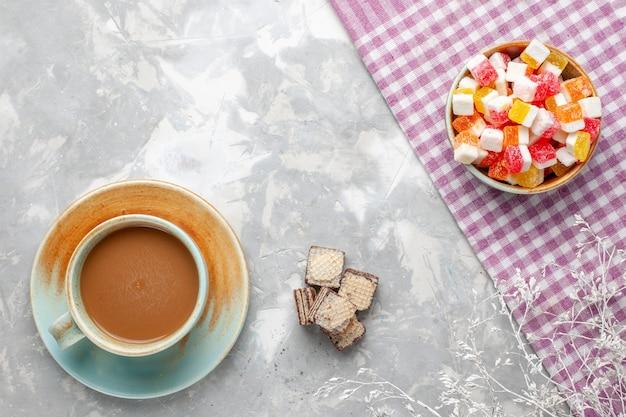 Vista dall'alto caffè al latte con cialde al cioccolato sullo sfondo chiaro zucchero dolce biscotto al cioccolato