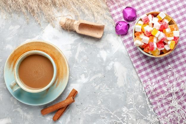 ライトデスクキャンディーグッディシュガースウィートにシナモンとキャンディーを添えたトップビューミルクコーヒー