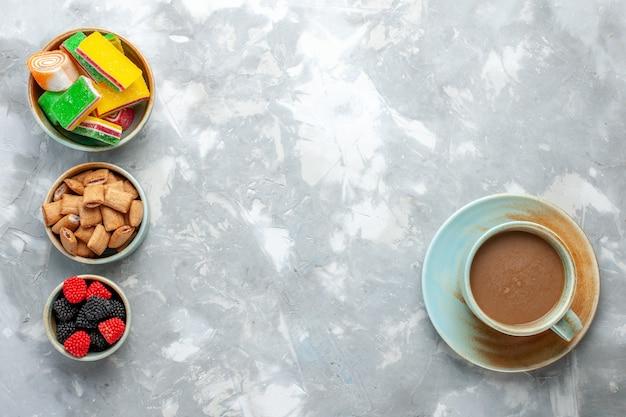 Vista dall'alto caffè al latte con biscotti berry-confitures e dolce sulla scrivania leggera caramelle dolci bonbon foto cool