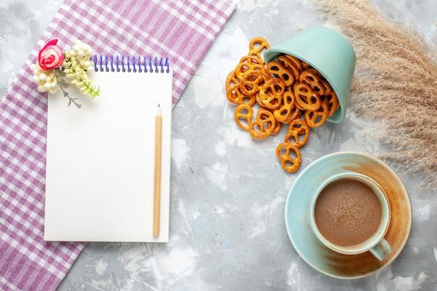 ライトデスクにメモ帳とクラッカーを備えたトップビューミルクコーヒーは、鮮明なカラー写真を飲みます