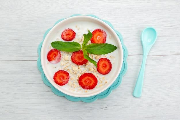 Вид сверху молоко с овсяной кашей внутри тарелки с клубникой на белом, хлопья для завтрака здоровья вкусно