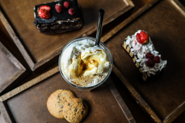 Вид сверху молочный коктейль с капучино в стакане с печеньем на подносе