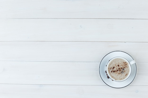 나무 배경에 컵에 상위 뷰 밀키 커피. 수평