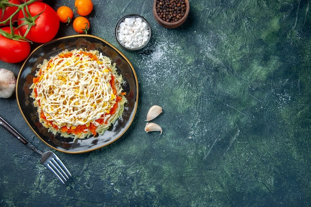 濃紺の背景に調味料と赤いトマトとプレートの内側の上面図ミモザサラダ