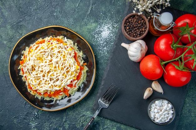 Vista dall'alto insalata di mimosa all'interno del piatto con condimenti e pomodori rossi su sfondo blu scuro Foto Gratuite
