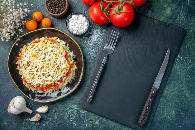 Vista dall'alto insalata di mimosa all'interno del piatto con condimenti e pomodori rossi su sfondo blu scuro