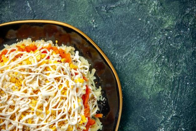 紺色の背景のプレートの中に卵ジャガイモと鶏肉の上面図ミモザサラダ