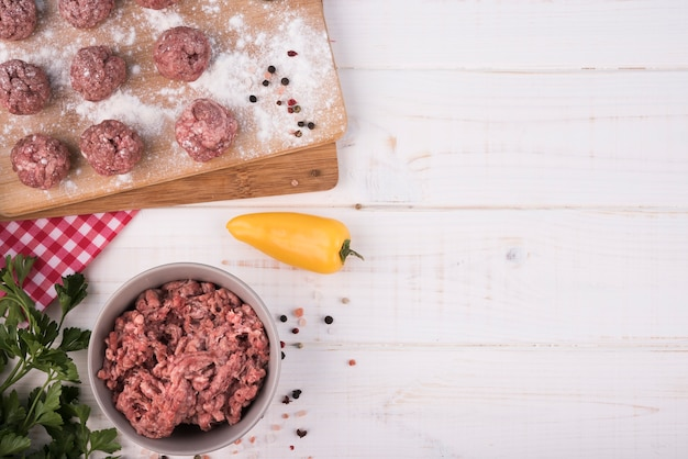 Top view minced meat and meatballs on wooden board with copy space