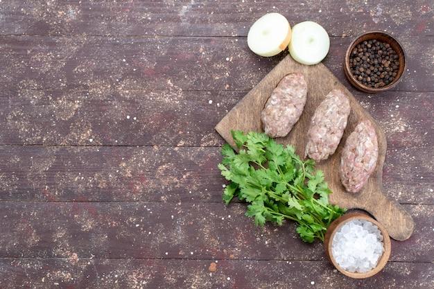 Вид сверху котлеты из сырого фарша, сформированные с зеленью, луком, солью на коричневом столе, мясное сырье, еда, зеленый