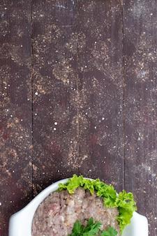 Vista dall'alto carne cruda macinata con verdure all'interno della piastra sulla foto di legno marrone carne cruda pasto cibo verde dello scrittorio