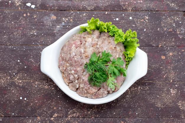 Вид сверху нарезанное сырое мясо с зеленью внутри тарелки на коричневом фоне мясное сырье еда зеленая фотография