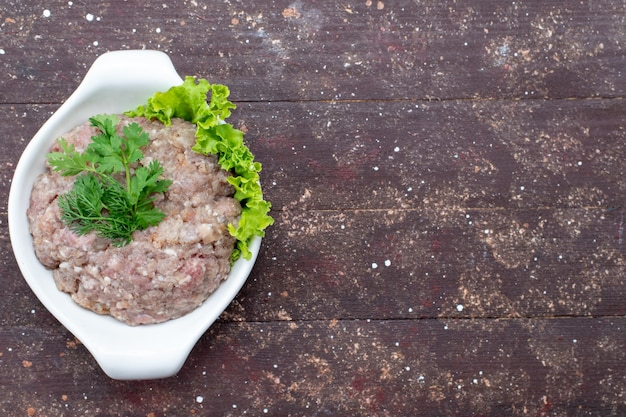 Вид сверху нарезанное сырое мясо с зеленью внутри тарелки на коричневом столе мясное сырье еда зеленая фотография