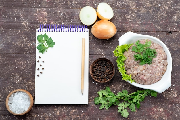 Vista dall'alto carne cruda macinata con verdure all'interno del piatto con cipolle e blocco note sullo sfondo marrone carne cruda pasto verde foto