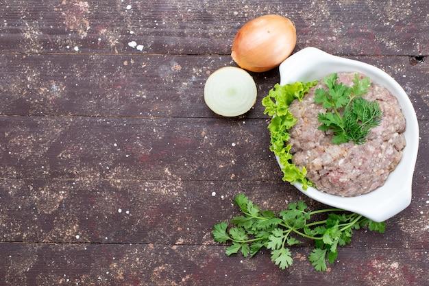 Вид сверху нарезанное сырое мясо с зеленью внутри тарелки с луком на коричневом фоне мясное сырье еда зеленая фотография