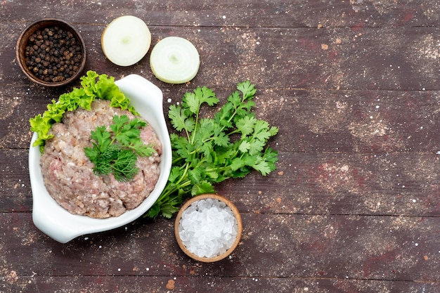 Top view minced raw meat with greens inside plate with onions salt on the brown background meat raw food meal green photo