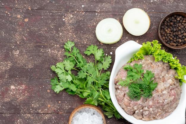 Vista dall'alto di carne cruda macinata con verdure all'interno del piatto con cipolle sale sulla foto di verde pasto cibo crudo carne scrivania marrone