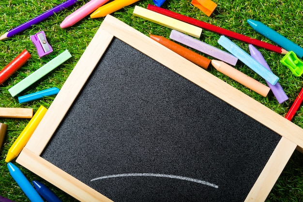 Top view of mini blackboard and colors on plastic grass