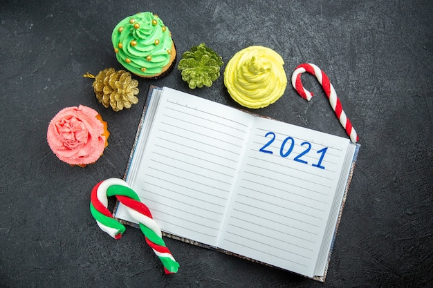 Vista dall'alto mini cupcakes colorati scritti su taccuino caramelle e ornamenti natalizi su sfondo scuro