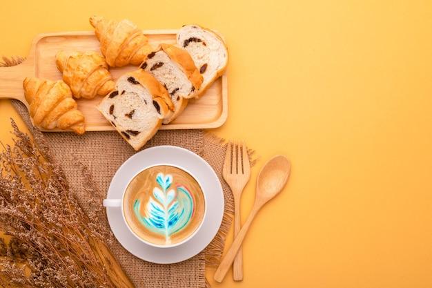 Вид сверху мини-круассан и хлеб в деревянной тарелке и кофе. концепция питания