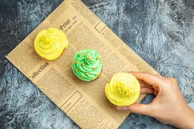 暗い表面の新聞でカップケーキを取る上面図ミニカップケーキ女性の手