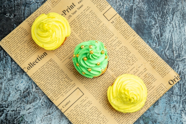 Top view mini cupcakes on newspaper on dark surface
