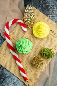 Vista dall'alto mini cupcakes caramelle di natale ornamenti di natale su scialle beige di giornale su superficie scura