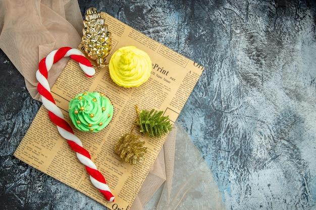 Вид сверху мини-кексы рождественские конфеты рождественские украшения на газетной бежевой шали на темной поверхности