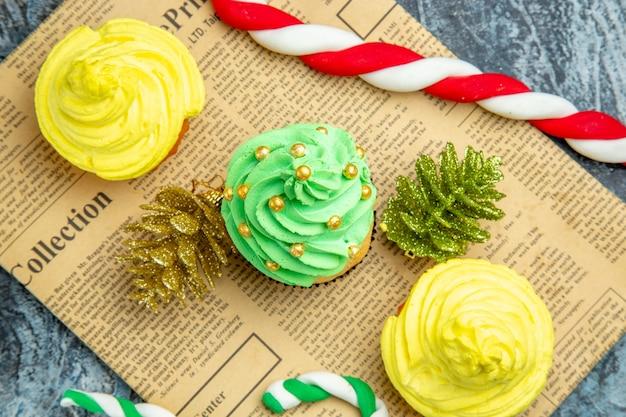 Vista dall'alto mini cupcakes ornamenti di natale caramelle sul giornale su superficie scura