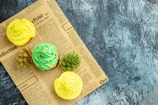 Top view mini cupcakes xmas ornaments on newspaper on dark surface