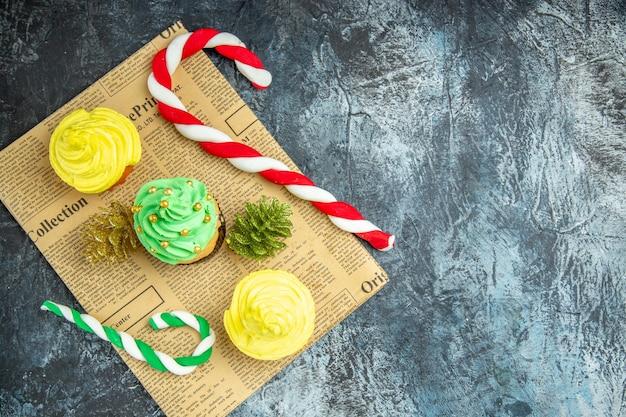 Vista dall'alto mini cupcakes ornamenti di natale sul giornale su superficie scura