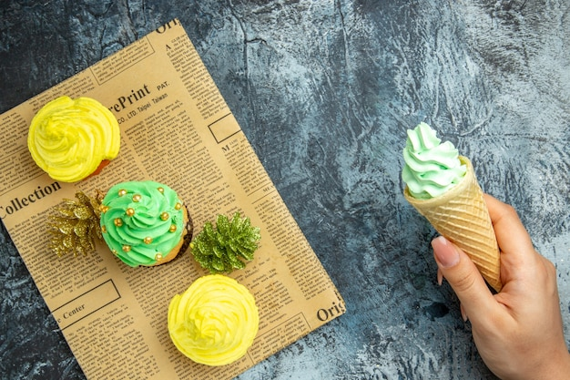 Top view mini cupcakes xmas ornaments on newspaper ice cream in female hand on dark surface