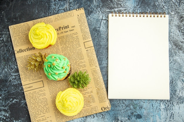 Top view mini cupcakes xmas ornaments on newspaper a notebook on dark surface