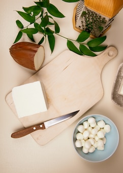Top view of mini mozzarella cheese in a blue bowl and various pieces of cheese on wooden cutting board with grater and ruscus on rustic leaves table