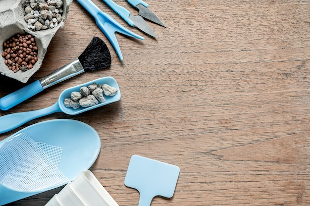 Top view mini set of gardening tools on wooden table, copy space.