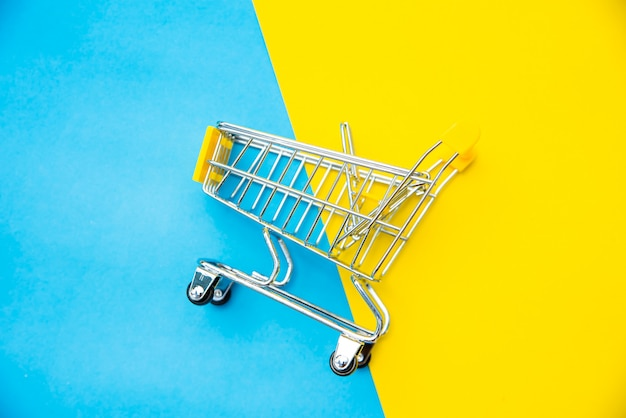 Top view for mini shopping cart on a colorful background.