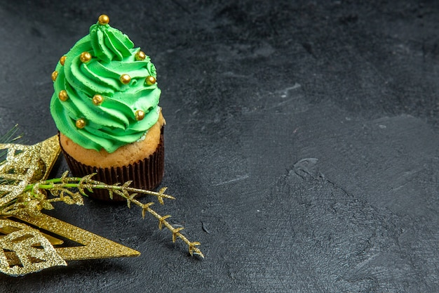 Top view mini xmas tree cupcake and golden hanging ornament on dark background free place