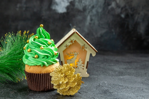 Vista dall'alto mini albero di natale cupcake natale albero ramo lanterna pigna dorata su superficie scura